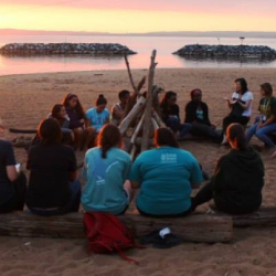 SEEDS students on a leadership retreat, sitting on the beach in a circle at sunset