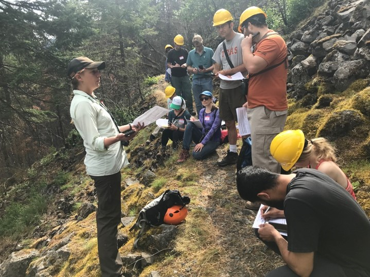 Woman (left) standing and explaining to group (right; on trail). Nearly all group members are wearing yellow hard hats. Group is in a forest, on a trail.