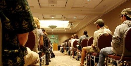 A walkway between attendees of a seminar leads to the speaker's podium.