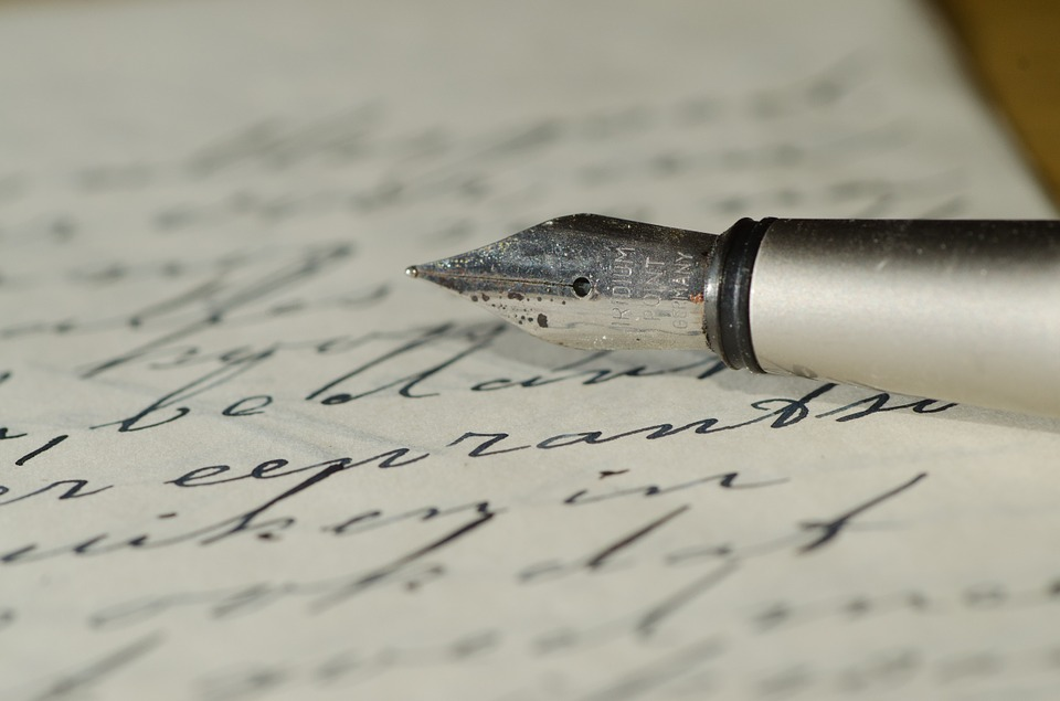 A caligraphy pen sits atop a piece of paper.