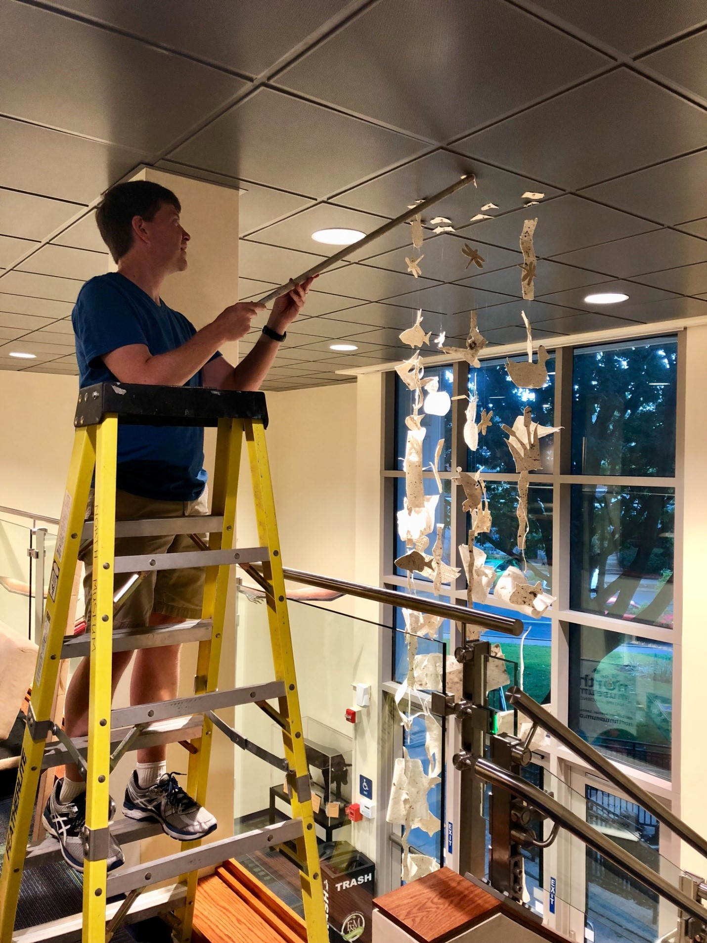 Man on a step ladder, hanging artwork from the ceiling. Artwork looks like a mobile.
