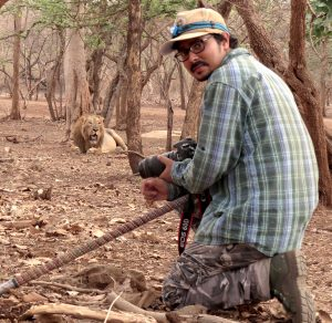 The author, wearing a baseball hat, glasses, a plaid shirt, and camouflage pants, holding a camera and looking back at the photographer. He is crouched, and in the background there are trees and a male lion.