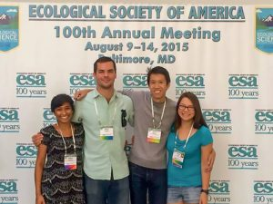 Group of four students standing in front of an Ecological Society of America 100th Annual Meeting banner