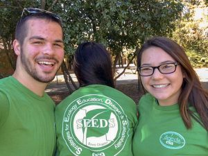 Three students in green shirts, one facing backwards to show their SEEDS shirt graphic