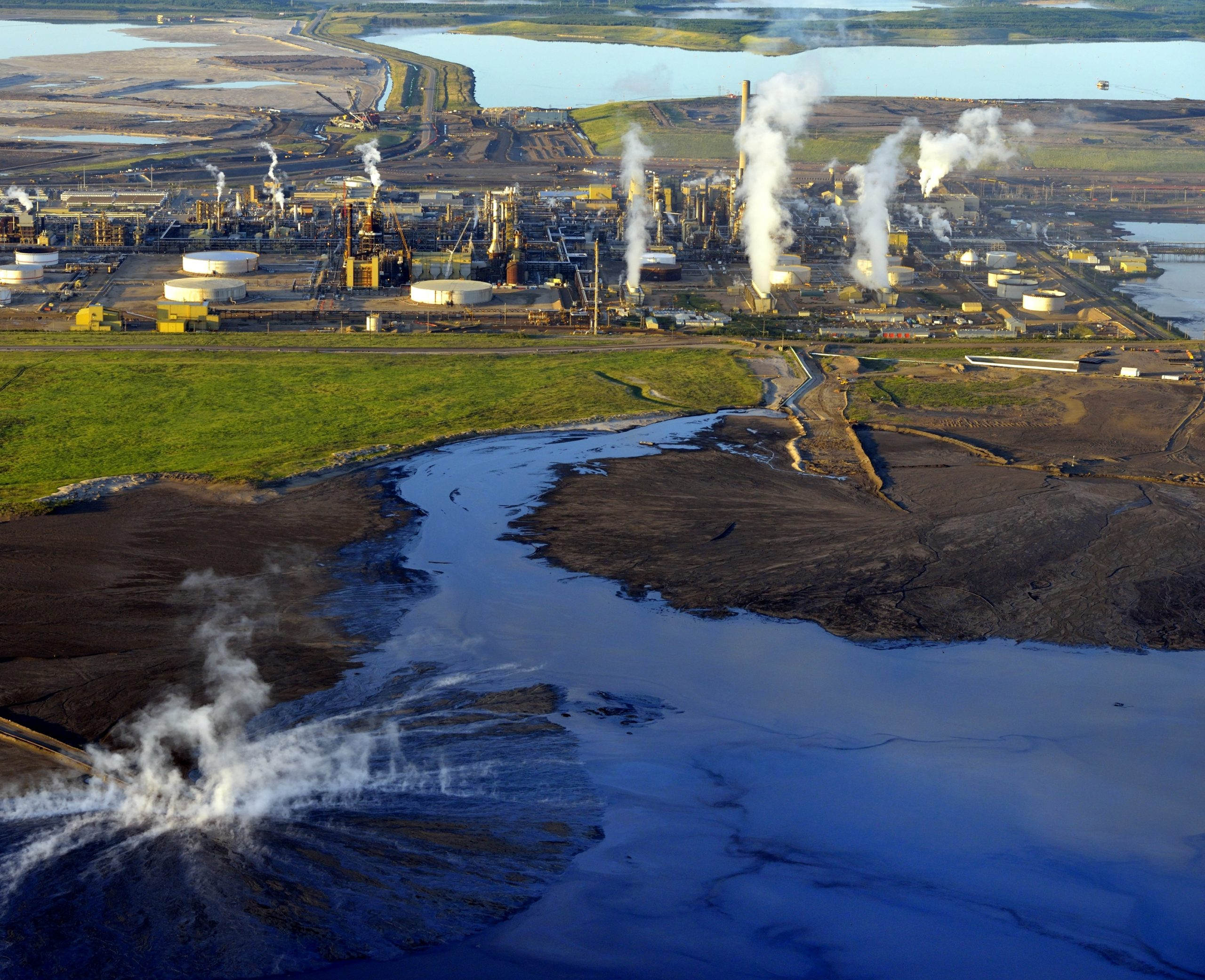 Steam at inflow to tailings pond at Syncrude's Mildred Lake bitumen refinery Oil sands north of Fort McMurray, Alberta
