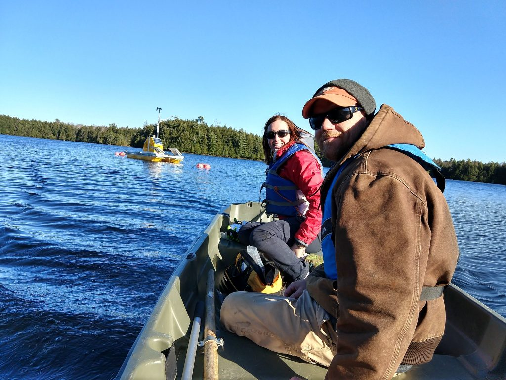 Two field technicians sit in a small raft or boat, looking back at the camera. Both are wearing coats and life preservers and have a bag full of gear between them. They are approaching a data collection station in the middle of a lake lined with evergreen trees. The data station is yellow and is fitted with several solar panels.