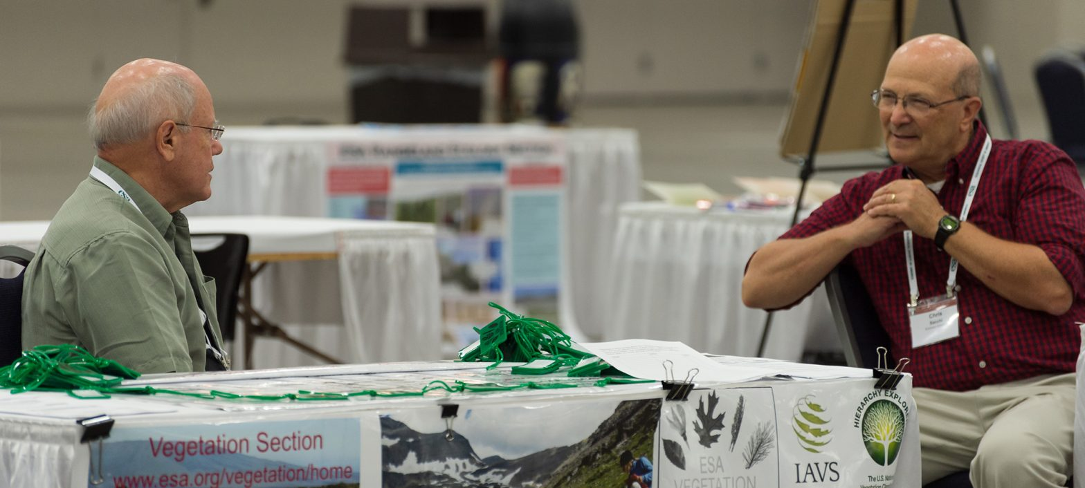 Two seated gentleman converse in the vegetation section booth at the 2019 Annual Meeting.