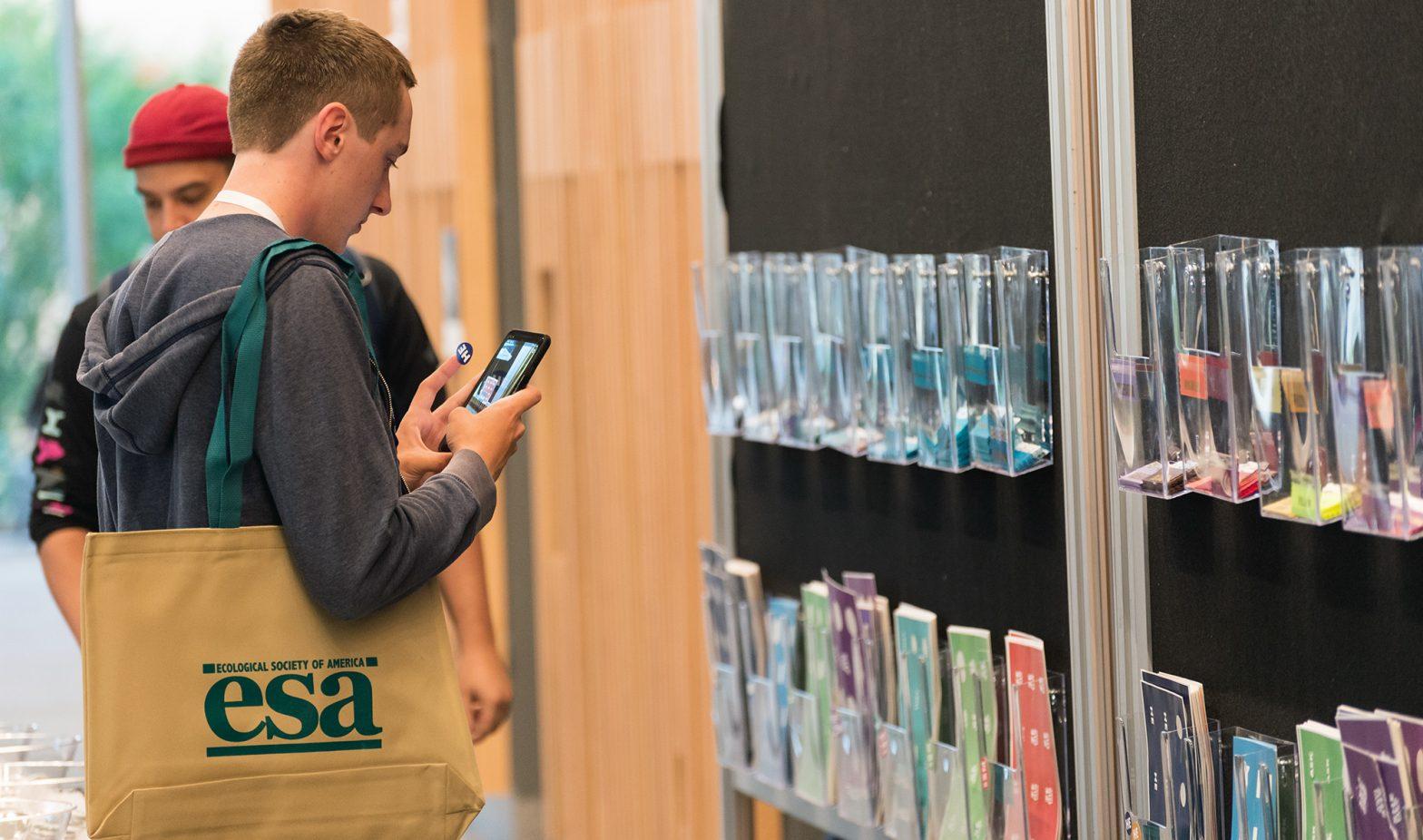 An ESA attendee at an in-person meeting checks their phone for meeting FAQs.