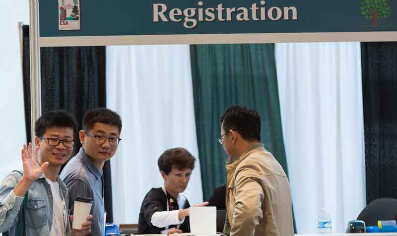 Three men wait to register at the 2019 annual meeting