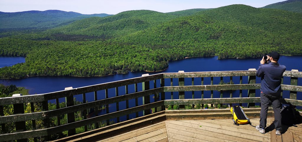 A man takes a picture of a green forest over a blue lake while standing at a lookout area.