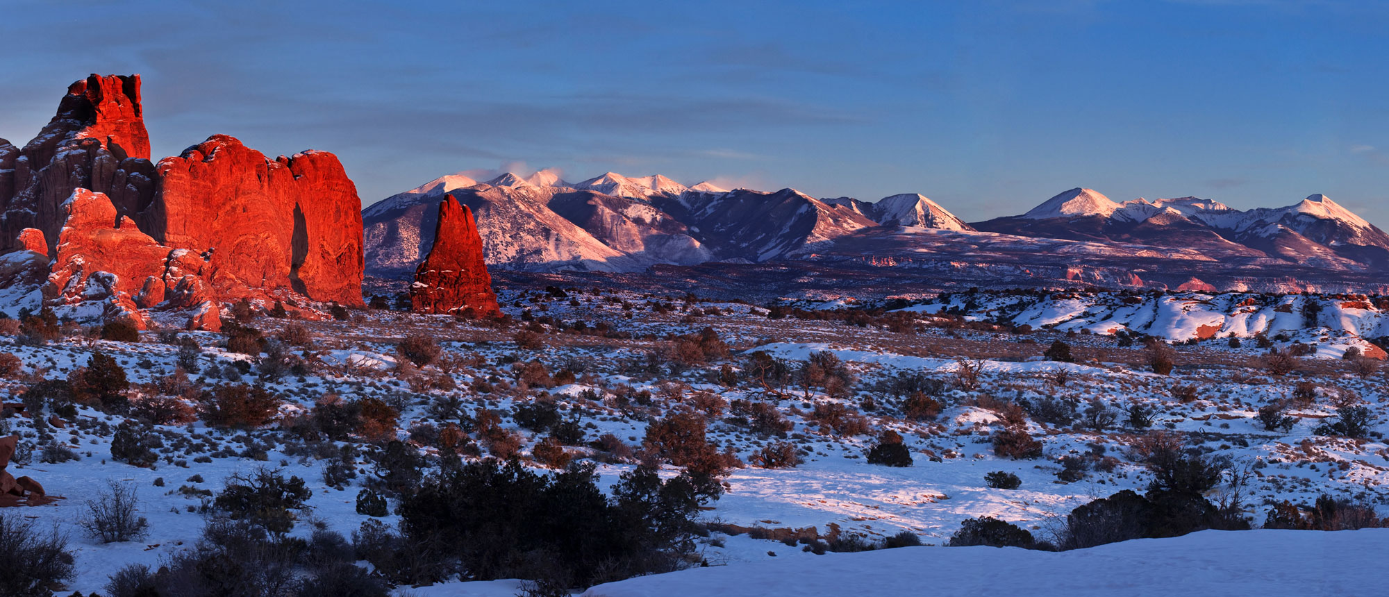 A snowy vista with white mountaintops in the distance and red clay formations in the foreground.