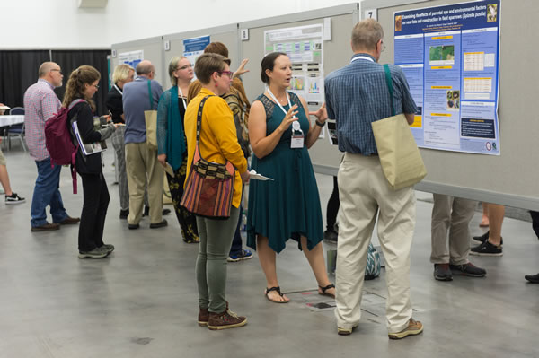 A group of ecologist discuss an informal poster session with the presenter.