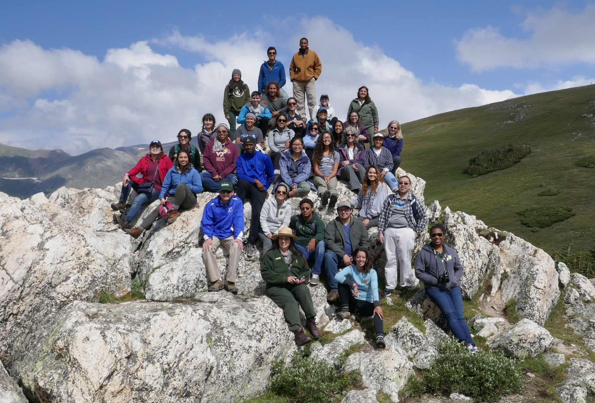 Group picture atop a large rock in a National Park with a ranger in the foreground.
