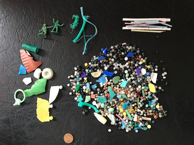 A cluster of small, colorful plastic pellets, broken shards, and small toys on a black leather surface. There is a 1-cent coin at the bottom of the photo for scale.